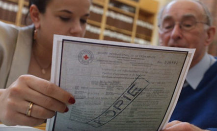"""A photo of two white people, who look at a piece of paper together, with the camera looking up at them from behind the paper. The paper is a scan of a historical document, with the word """"Kopie"""" stamped across it."""