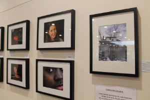 A photograph of the exhibit, which shows small photographs, framed in black frames, hanging on a white wall.