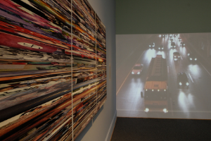 A photo of an exhibit, showing a projected video of cars and trucks on a highway on one wall. Next to it, on another wall, is an artwork featuring many different lines and stripes in different colors.