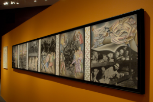 A photo of the exhibit, featuring a long span of artworks framed and hanging on an orange wall. The artworks feature photographs and illustrations, combined together.