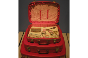 A photo of three red suitcases, the biggest on the bottom and the smallest on top. The smallest is open to reveal personal objects displayed.