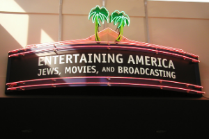 """A photo of a miniature theatre marquee, with red light stripes above and below the text. Two palm trees, made out of neon lights, are on top in the middle. The words """"Entertaining America: Jews, Movies, and Broadcasting"""" is in white on a black background in the middle of the marquee."""