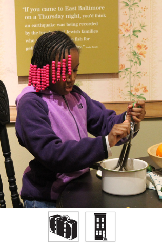 A young student plays with a toy in our Voices of Lombard Street exhibit, pretending to make Shabbat dinner.