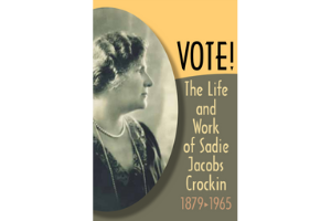 "A black and white photo of Sadie Cockrin, a white woman wearing pearls and a dark dress, in profile. Next to the image is the word ""Vote!"" in black on a yellow-orange background. The words ""The Life and Work of Sadie Jacobs Cockrin"" are below it, in the same yellow-orange color on a brown background. ""1879-1965"" is written below that in a grey-pink color."