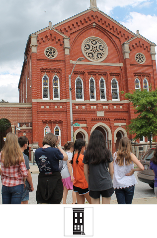 A group of older students stand outside B'nai Israel synagogue, a large brick building with specially designed windows and architecture. The students look at the synagogue.