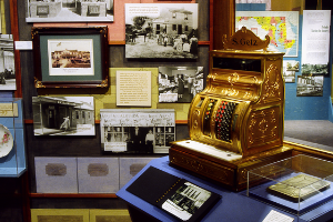 A photo of the exhibit, featuring framed pictures and panels of text in the background, and a golden-colored, old-fashioned register, on a stand in the foreground.