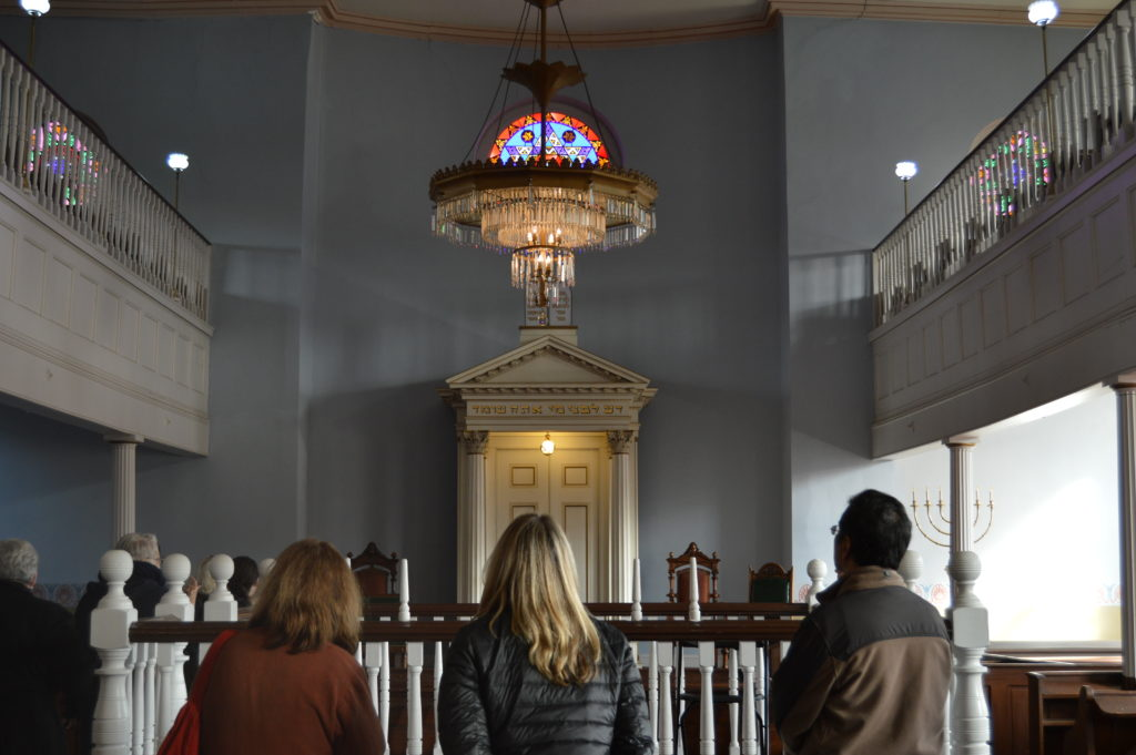 Three people stand inside the sanctuary of the Lloyd Street Synagogue with their backs to the camera. They are facing the bimah. In the background of the photo is the ark and stained glass window.