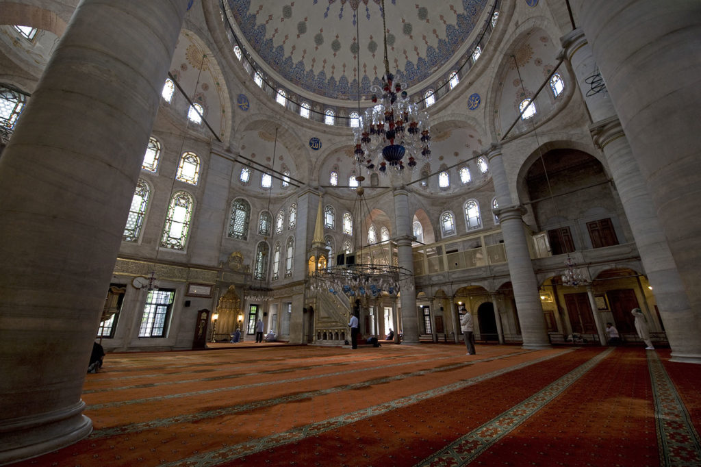 Color photo showing the interior of an Islamic house of worship. There is a red and orange wall-to-wall carpet on the floor and the walls are light stone with many windows. A chandelier hangs in the center.
