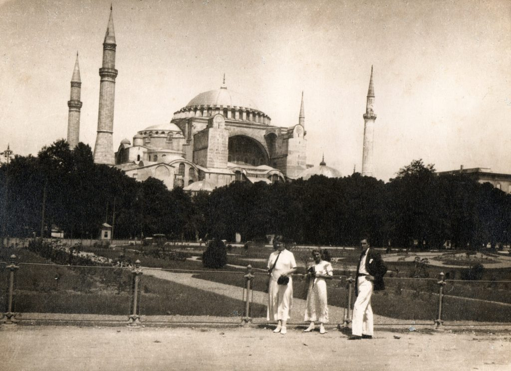 Sepia photograph showing three tourists (two women and one man) standing in front of a large garden in front of the Hagia Sophia. The building is large and made of stone. It has at least two domes and four spinaret towers.