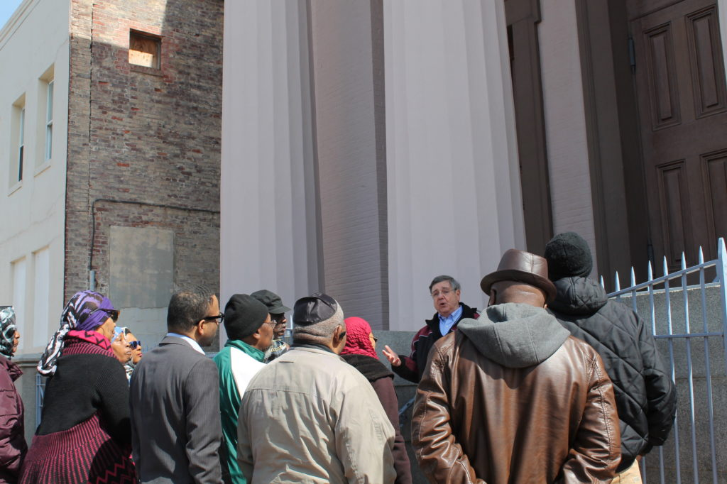 A group of people in winter coats stand outside the Lloyd Street Synagogue as they listen to a docent begin a tour.