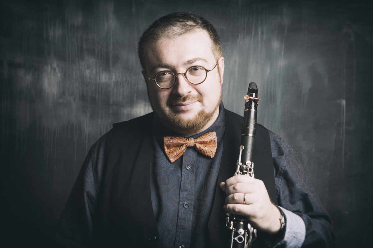 A white man wearing glasses and an orange bowtie holds a clarinet.