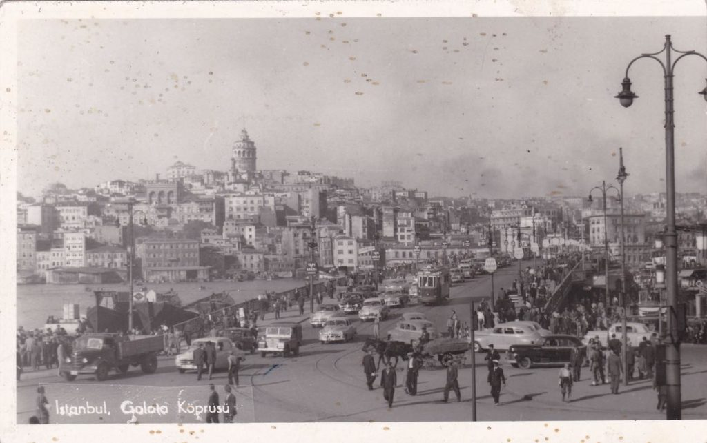 """Black and white photo postcard showing a bridge full of cars, trucks, trolleys and people on foot. A large city can be seen in the background.  Text on image reads """"Istanbul, Golota Koprusu"""" [German]."""