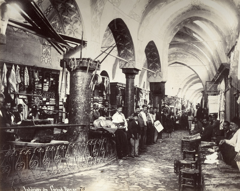 Sepia photograph showing the interior of a covered market. shops and shop keepers can be seen on the left side of the image in between large stone arches. on the right a variety of men are seated or squatting against the wall.