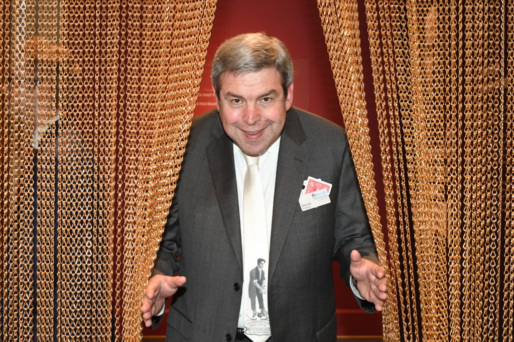 Color photo of an older white man wearing a suit and tie. He is smiling and holding open a gold chain curtain.