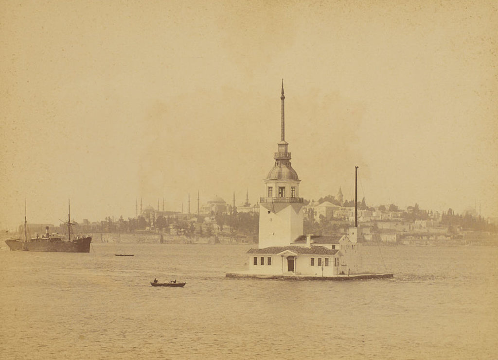 Sepia photo of a small white building with a spire in the middle of water. Some boats are visible around it and the coast of Istanbul can be seen azily in the background.