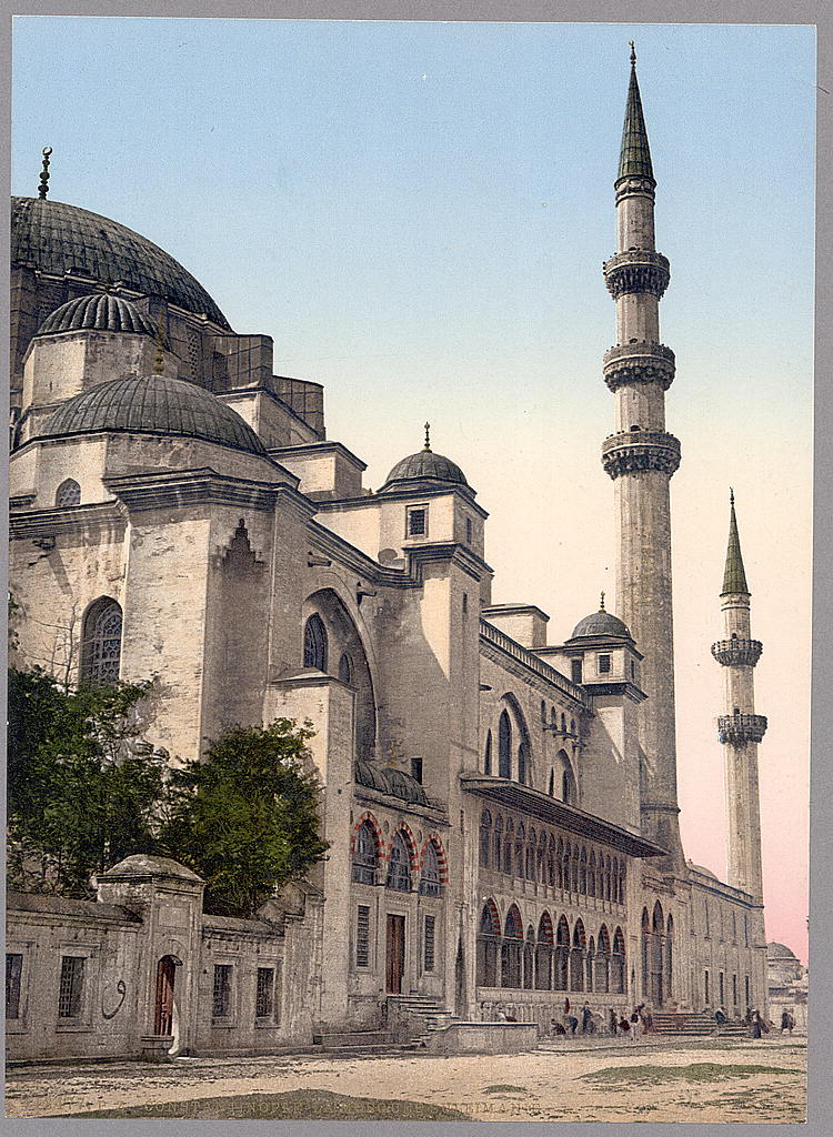 Colorized photograph of a large stone building, specifically an Islamic mosque. Two spinnaret towers arevisible on the left along with a number of distinctive architectural domes.