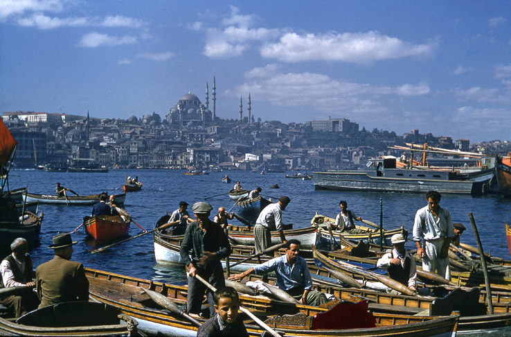 Color photograph showing a number of men in small rowboats in the foreground. Behind them can be seen more small boats out in the water. The large city of Istanbul is seen in the background.