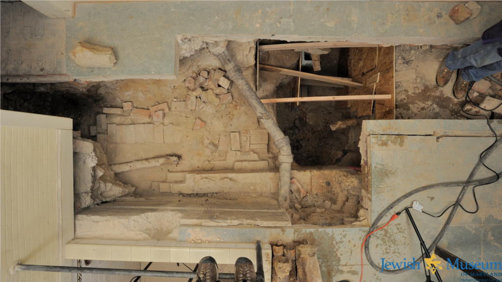 An overhead picture of an excavation site, showing a deep hole in the floor and pipes and bricks in the hole.