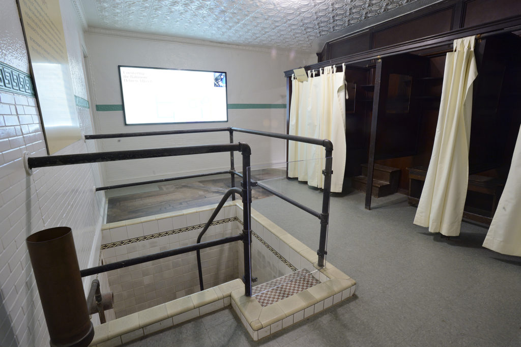 Panoramic view of a room with a mikvah in the foreground and changing stalls in the background.