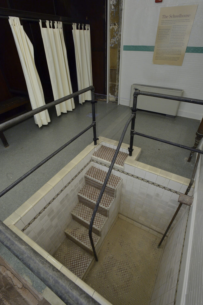 Interior view of a ritual bath. The bath is recessed into the floor. There are are six steps to reach the floor of the bath. There is red and white checkered ceramic tiles on the floor and stairs. The walls of the bath are covered in white tiles with a decorative patterned running about a foot from the top. There are metal handrails around the bath.