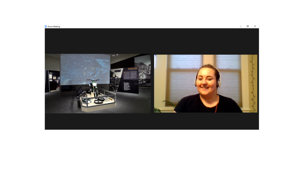 A screenshot of a Zoom meeting. Talia, a white woman, is smiling on the rights side, and there's a photo of the Scrap Yard exhibit on the left.