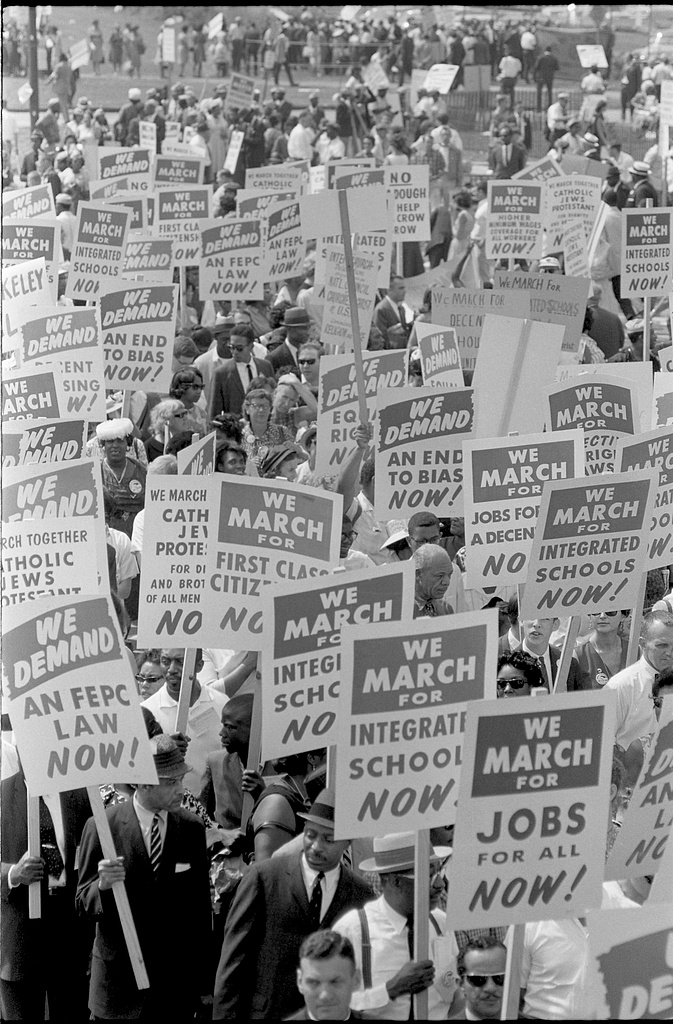 """Black and white photograph of a crowd of marchers hold signs with messages like """"We March for Integrated Schools Now,"""" """"We March for Jobs for all Now,"""" """"We Demand an FEPC Law Now,"""" and similar."""