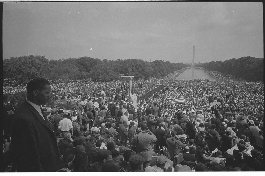 Alt text: Black and white photograph of an enormous crowd of people. The Washington Monument and reflecting pool are visible in the back of the photograph. The entire field between the photographer and the monument is full of people. An American flag can be seen held up near the middle of the photo.
