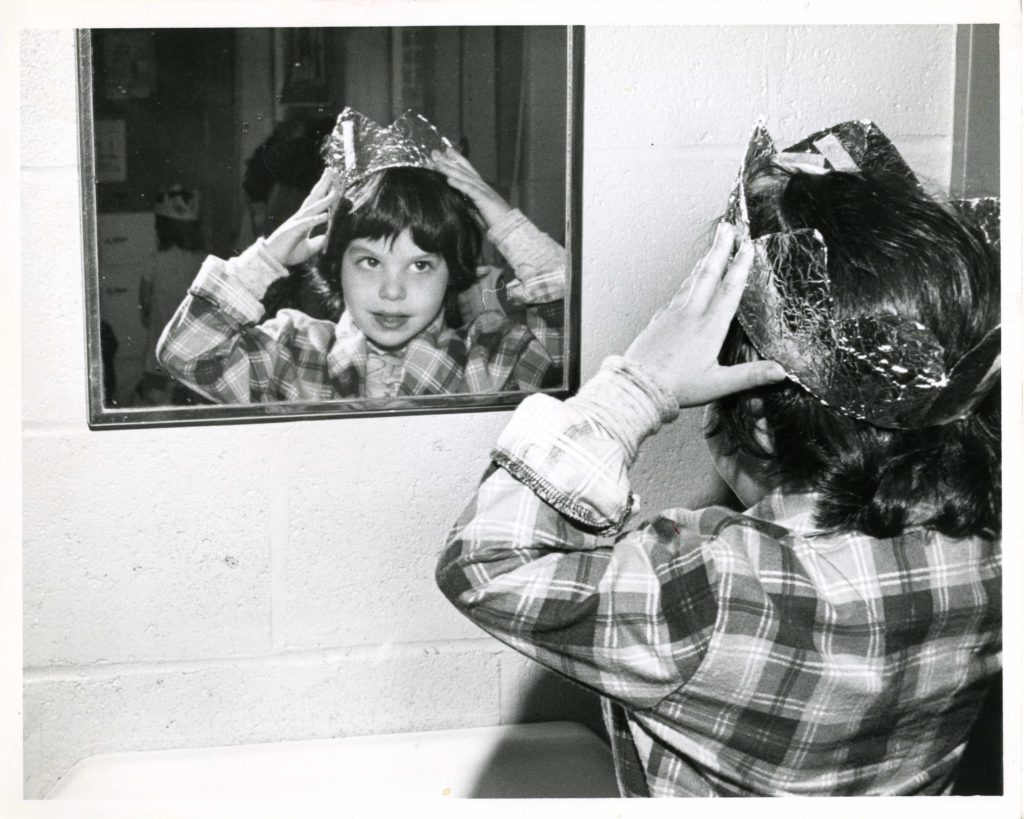 a young child looks into a mirror while putting a crown on his head.