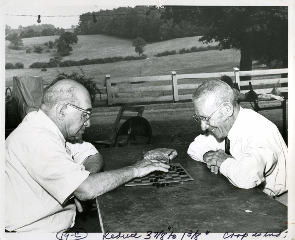 Two older white gentlemen sit at an outdoor table playing checkers.