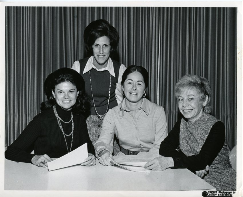 Black and white photo of four white women, 3 seated at a desk holding papers.