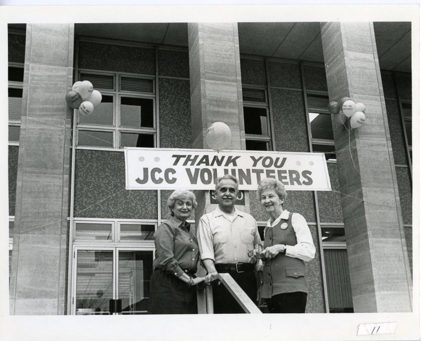 """3 older white adults stand outside a large building. A sign behind the reads """"Thank You JCC Volunteers."""""""