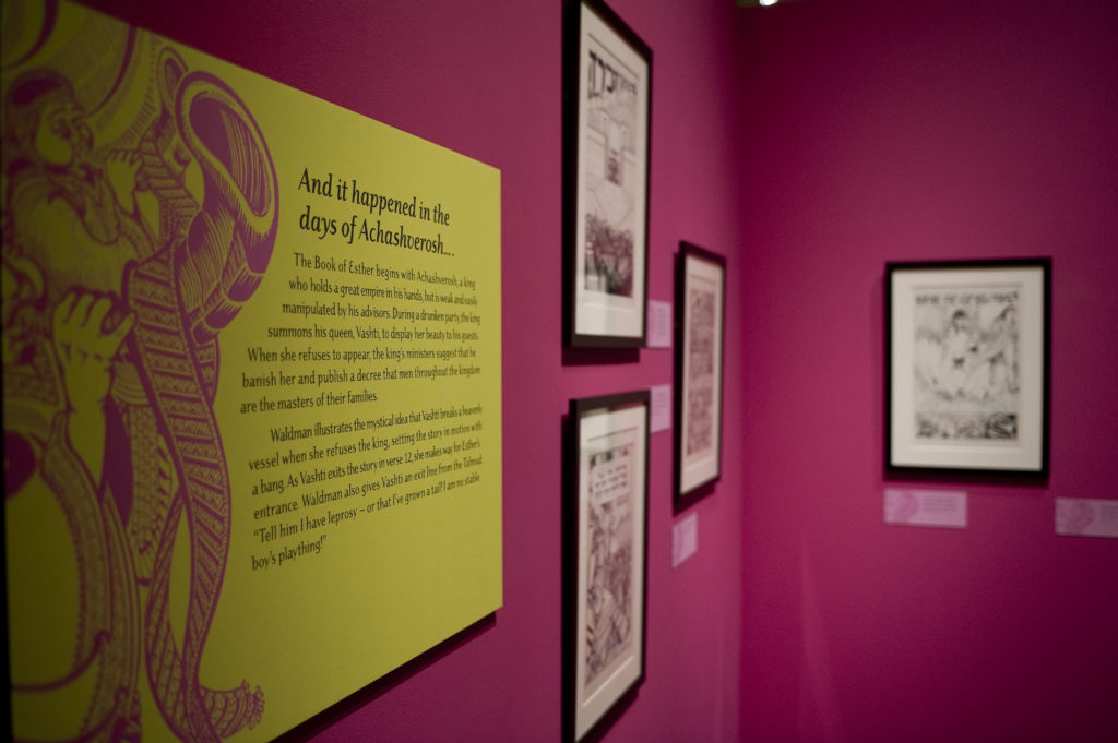 installation shot of the Drawing on Tradition exhibit, showing framed illustrations from the book of Esther on a hot pink wall and a lime green text panel.