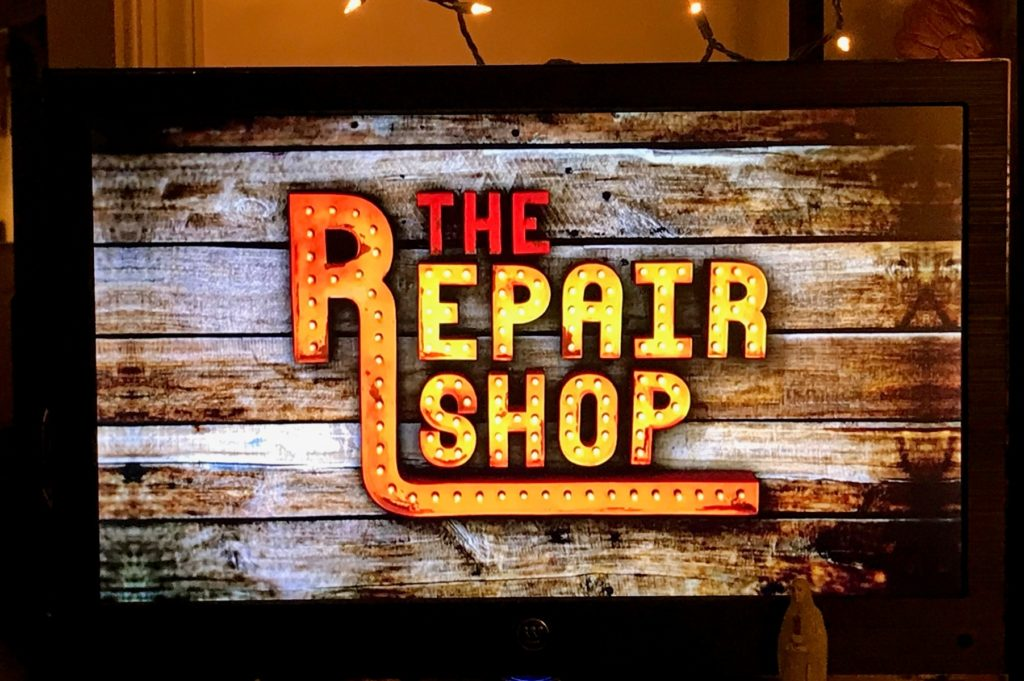 scene from Repair Shop captured on the author's television, showing the title in lights on the side of the building