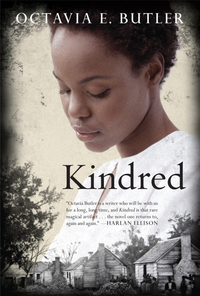 Kindred book cover showing A young Black girl looking down over a set of black and white wooden cabins.