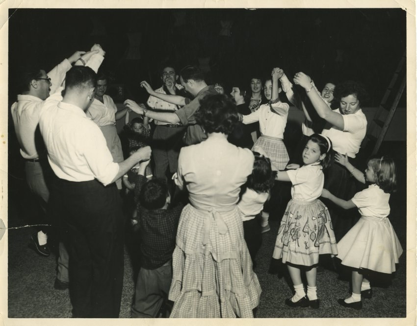 children and adults dancing in a circle