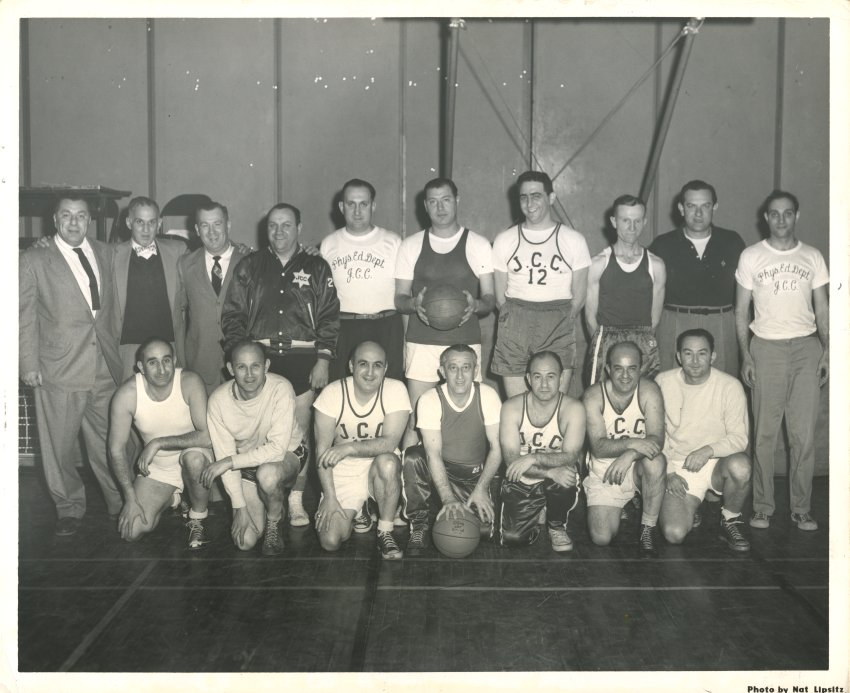 Men in suits and basketball gear pose for the camera.