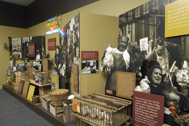 Section of exhibit with historic photographs, quotes, and props. In the foreground are cut-outs of a butchers holding chickens.