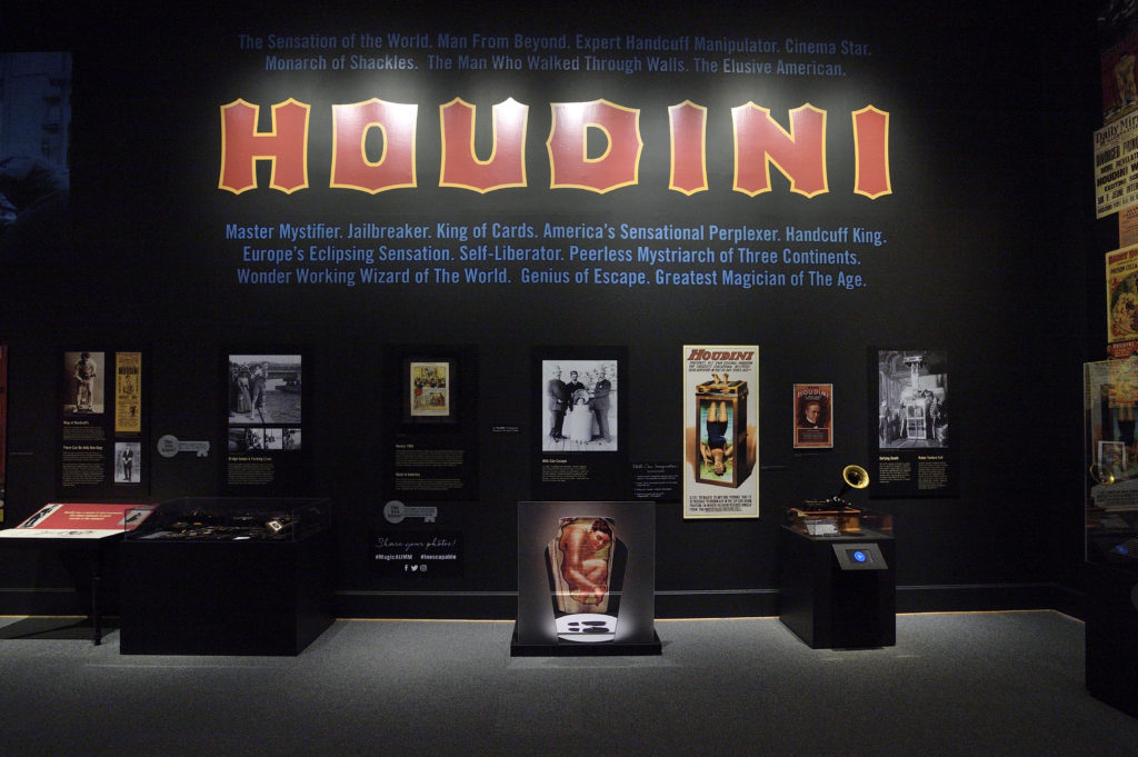 """Section of the exhibit that shows artifacts in cases on the floor, photos and text panels on the wall at eye level, and above """"HOUDINI"""" in red lettering."""