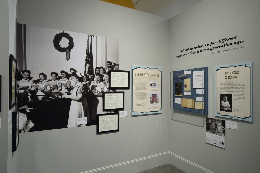 Interior room of exhibit with panels and archival documents hung on the walls. Taking up the majority of the image is a black and white photo showing nursing students singing around a piano with a wreath hung behind them.