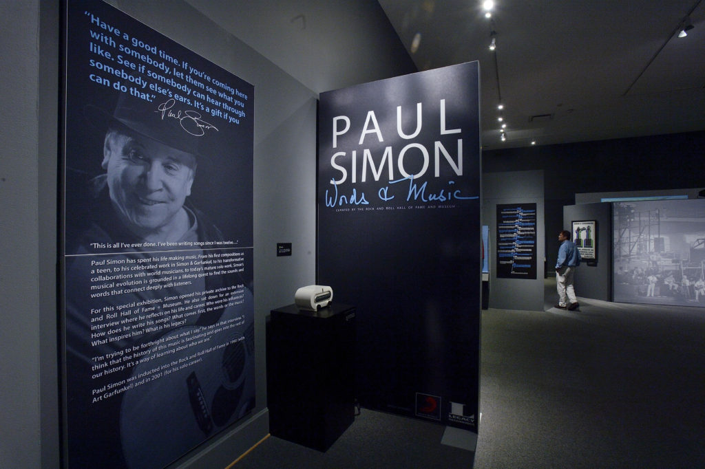 The entrance of the exhibit space. To the left there is a large panel hanging on the wall with a photo of Paul Simon and illegible text. To the right in the background is a person walking through the space.